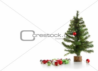 Small artifical tree with ornaments on white