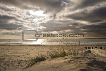 Beautiful sunset image with sun rays and beach