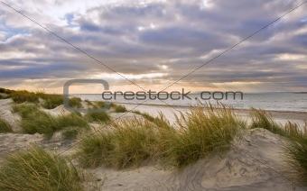 Beautiful sunset image with sun rays and beach
