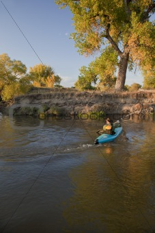 kayaker paddling across a river