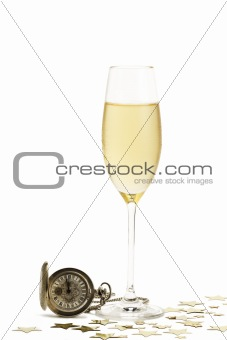 cold glass of champagne with a old pocket watch and stars