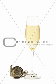 cold glass of champagne with a old pocket watch