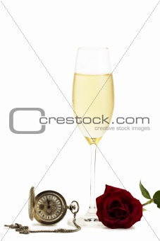 cold glass with champagne with a red rose and a old pocket watch