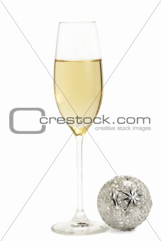 glass of champagne with a metal christmas ball