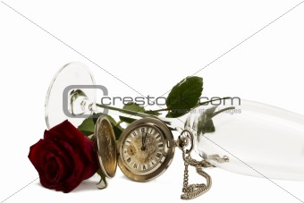 old pocket watch with a red wet rose under a lying champagne glass