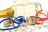 two glasses with champagne, old pocket watch, streamer, cork and confetti in front of a champagne bottle