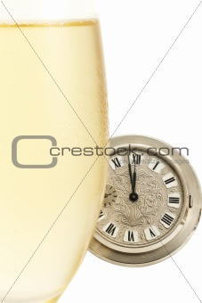 old pocket watch behind a cold glass with champagne