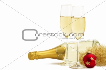 two glasses of champagne with angels hair, red christmas ball in front of a champagne bottle