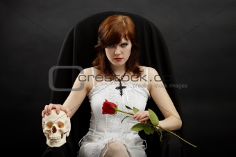 Beautiful girl sitting in chair with skull and rose