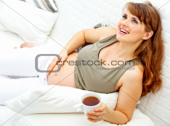 Smiling beautiful pregnant woman relaxing on couch and  holding cup of tea in hand