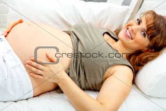 Smiling beautiful pregnant female lying on sofa and  holding her belly.