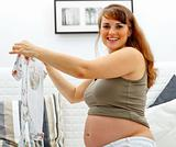 Smiling beautiful pregnant female sitting on sofa with baby clothes  in hands.