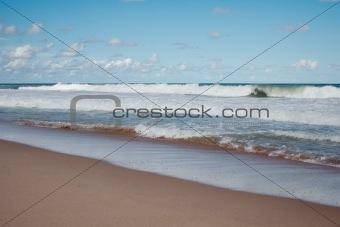 Waves breaking on the sandy beach.