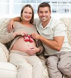 Lovely couple putting baby shoes on the woman&#39;s belly