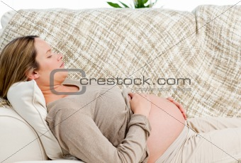 Tired pregnant woman relaxing on her sofa