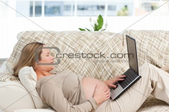 Smiling pregnant woman using her laptop lying on the sofa