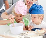 Two children and their mother stiring a preparation for cookies