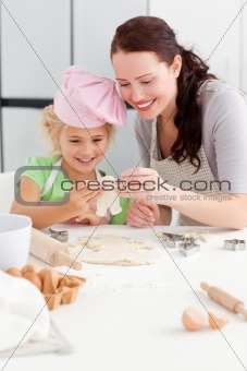 Cheerful mother and daughter making cookies in form of a man