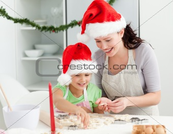Adorable girl with her mother baking Christmas cookies