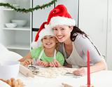 Portrait of a cute girl with her mother baking Christmas cookies