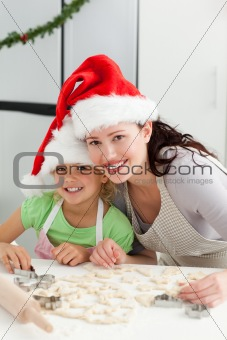 Beautiful mother and daughter cooking Christmas biscuits