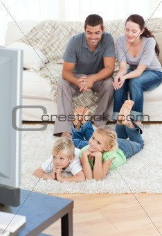 Adorable siblings watching television with their parents