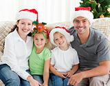 Cheerful family with Christmas hats sitting on the sofa