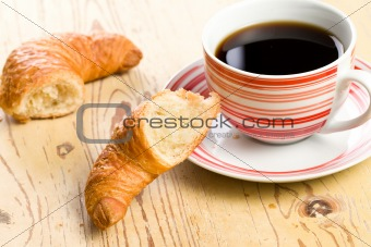 breaking croissant with coffee