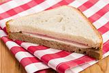 ham sandwich on checkered napkin
