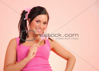 Beautiful happy teenage girl with a heart shaped lollipop . pink