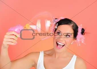Beautiful happy teenage girl blowing soap bubbles and having fun