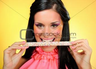 Beautiful happy woman with a hali gali sweet lollipop . yellow b