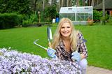 Pretty woman with gardening tools outdoors near flower hill