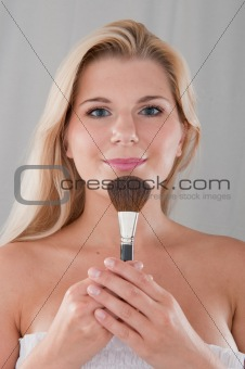 beautiful girl applying powder make-up with brush