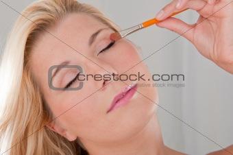 beautiful girl applying eye make-up with brush