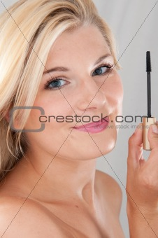 beautiful girl applying black eye mascara
