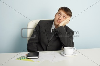 Businessman pensively looks upwards