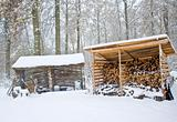 Firewood timber stack shed in snow covered forest