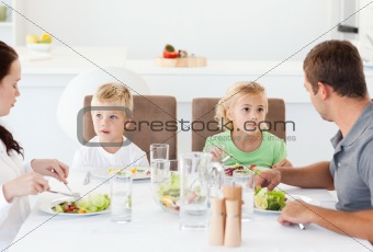 Serious family eating a salad at lunch in the kitchen