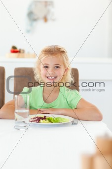 Smart girl sitting at a table to eat her healthy salad