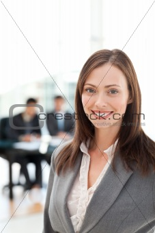 Attractive woman during a meeting with two businessmen sitting in the background