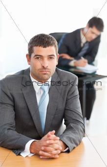 Charismatic businessman sitting in the foreground while his coll