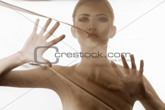 portrait of nude girl behind material