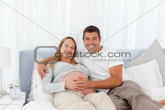 Attentive man touching the belly of his wife