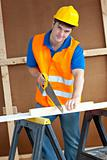 Charismatic male worker wearing a yellow hardhat sawing a wooden