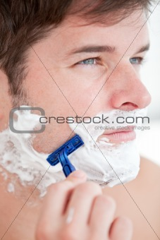 Bright caucasian man shaving in the bathroom
