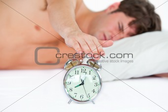 Asleep young man stopping his ringing alarm clock in the bedroom