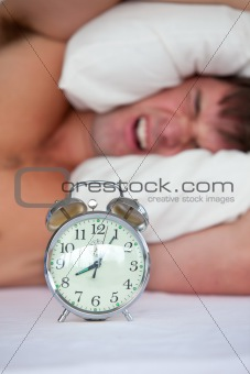 Angry young man lying in bed and annoyed by his alarm clock in t