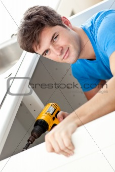 Charismatic man repairing his sink and holding a drill in the ki