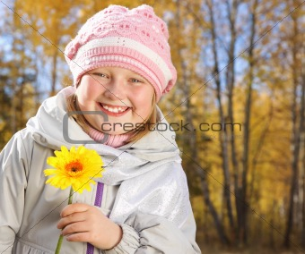 Portrait of smiling little girl with a yellow flower in the autumn forest.